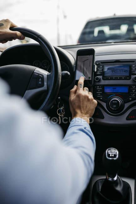 Nahaufnahme eines Mannes mit tätowierter Hand am Steuer mit Handy als Navigationssystem — Stockfoto