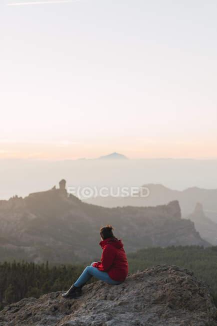 España, Gran Canaria, Pico de las Nieves, mujer sentada en la roca mirando hacia la vista. - foto de stock