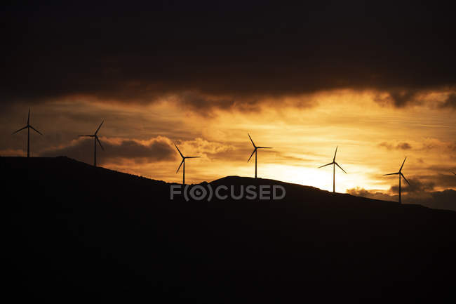 Spain, Andalusia, Tarifa, wind wheels on mountain at sunrise — стоковое фото