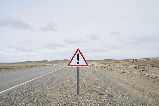 Argentina, Patagonia, Strada vuota con cartello del punto esclamativo in mezzo al deserto — Foto stock
