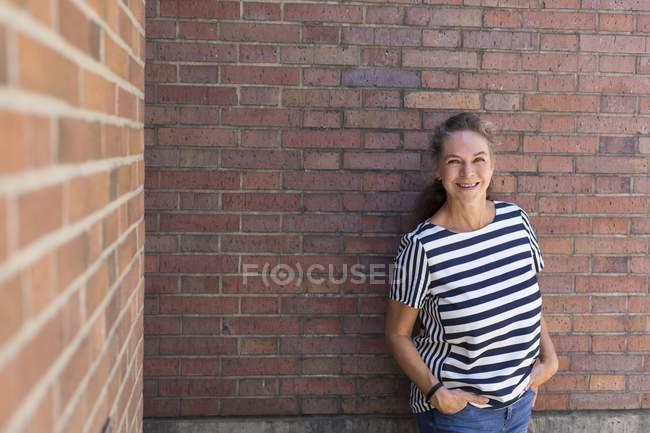Ritratto di donna matura sorridente appoggiata al muro di mattoni in estate — Foto stock