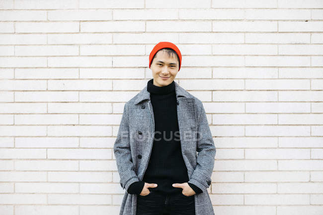 Portrait of stylish young man wearing cap, black turtleneck pullover and grey coat — стокове фото