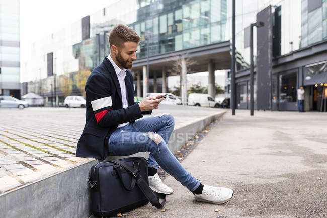 Stylish businessman sitting in the city using cell phone — Stock Photo
