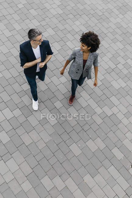 Vue de dessus de deux collègues marchant et parlant sur une place — Photo de stock