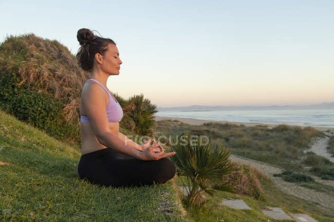 Woman meditating on the beach in the evening — Stock Photo