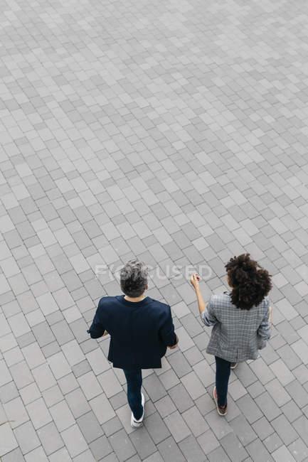 Draufsicht auf zwei Kollegen, die auf einem Platz gehen — Stockfoto
