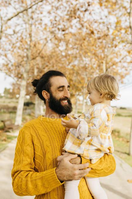 Padre cargando a su hija en un día de la mañana en el parque en otoño - foto de stock