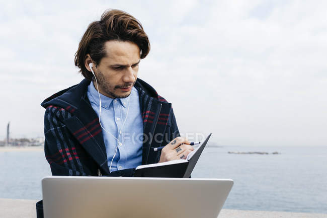 Spain, Barcelona, man sitting at the sea working with laptop and notebook — Stockfoto