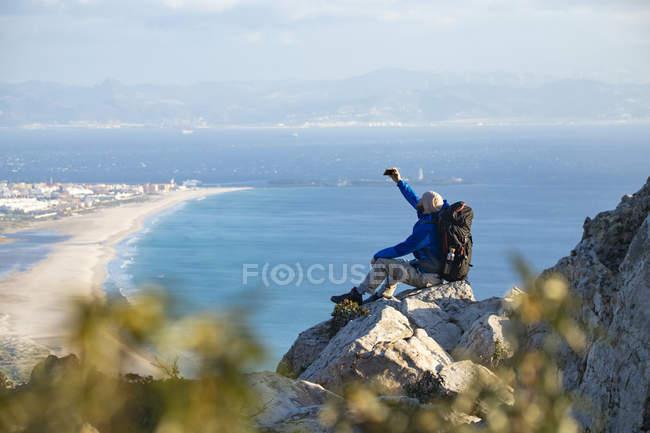 Cádiz, Andalucía, Tarifa, el hombre en un viaje de senderismo en la costa sentado en una roca tomando una selfie - foto de stock