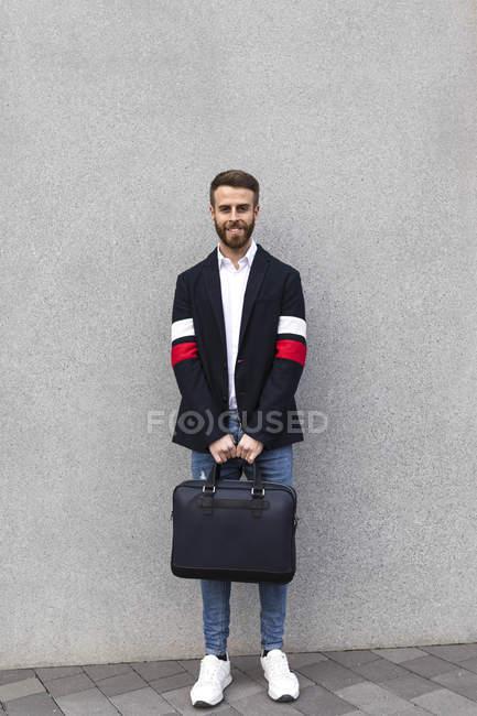Retrato de un hombre de negocios con estilo frente a la pared gris. - foto de stock