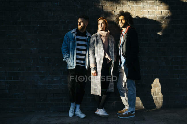 Three serious friends standing at a brick wall in shadow — Stock Photo