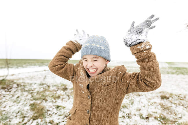 Happy boy playing with snow in winter — Stock Photo