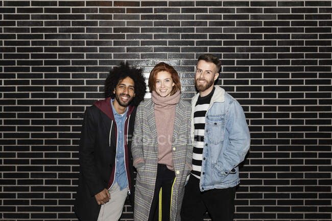 Portrait of three smiling friends standing at a black wall — Stock Photo