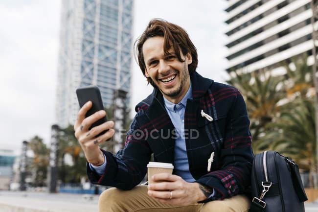 Espagne, Barcelone, homme heureux assis dans la ville avec café à emporter et téléphone portable — Photo de stock