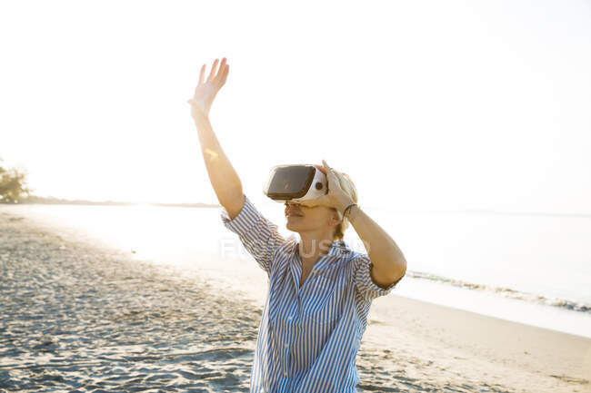 Thaïlande, femme portant des lunettes de réalité virtuelle sur la plage à la lumière du matin — Photo de stock