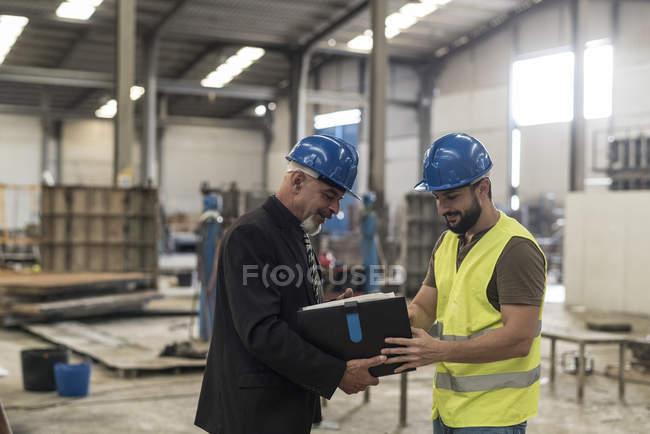 Geschäftsmann mit Ordner im Gespräch mit Arbeiter in Fabrik — Stockfoto