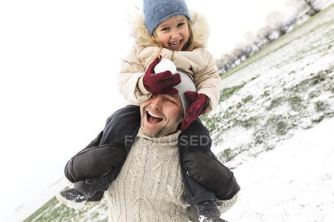 Padre giocoso che porta figlia a cavalluccio nel paesaggio invernale — Foto stock