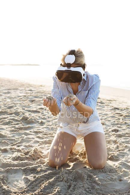 Tailândia, mulher usando óculos de realidade virtual na praia na luz da manhã — Fotografia de Stock