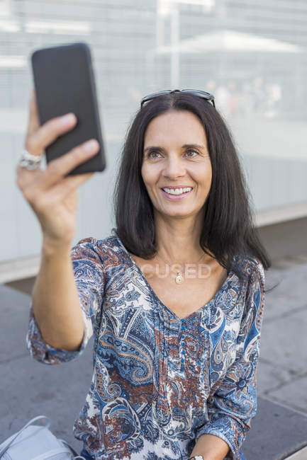 Portrait of smiling mature woman taking selfie with smartphone — Stock Photo