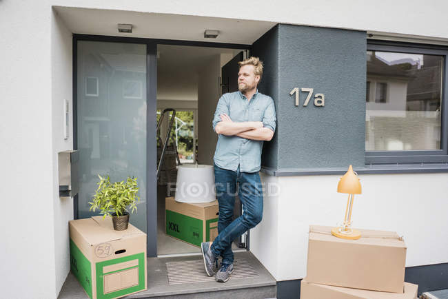 Man standing at house entrance surrounded by cardboard boxes — Stock Photo