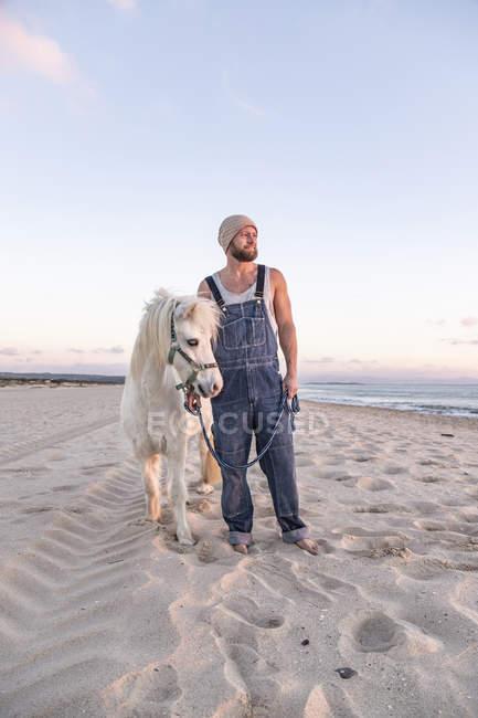 Испания, Уфа, человек с пони, стоящий на пляже — стоковое фото