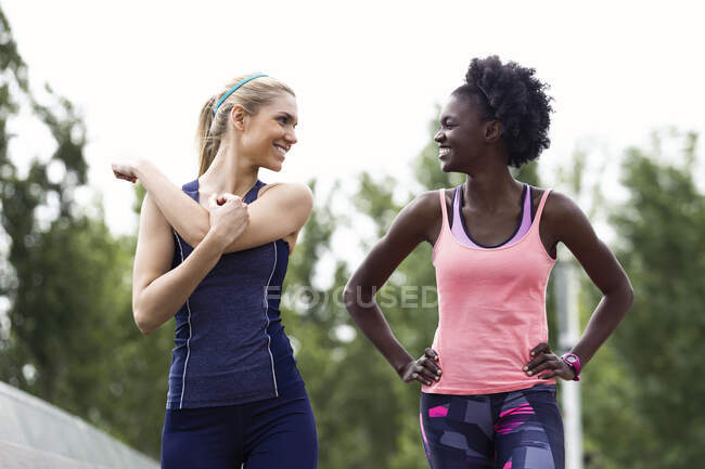 Two sporty young women talking and relaxing after running in the city — Stock Photo