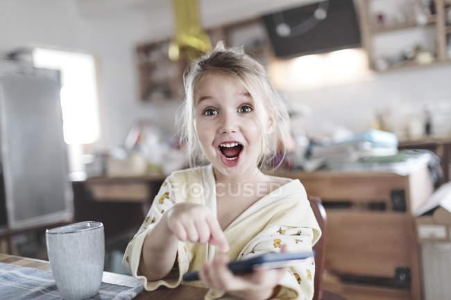 Портрет взволнованной маленькой девочки на кухне, указывающей на смартфон — стоковое фото