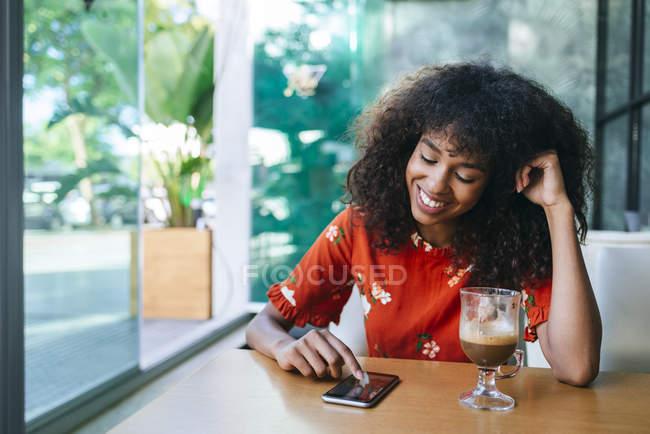 Ritratto di giovane donna sorridente in caffetteria con cellulare — Foto stock
