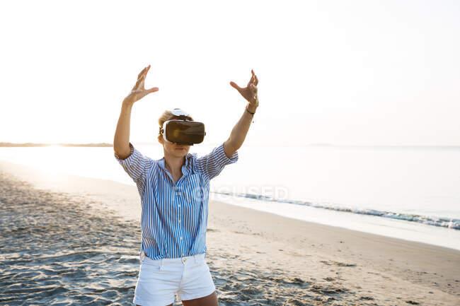 Bionda donna fare tipo di esercizi di yoga su una spiaggia in Thailandia con occhiali realtà virtuale 3D — Foto stock