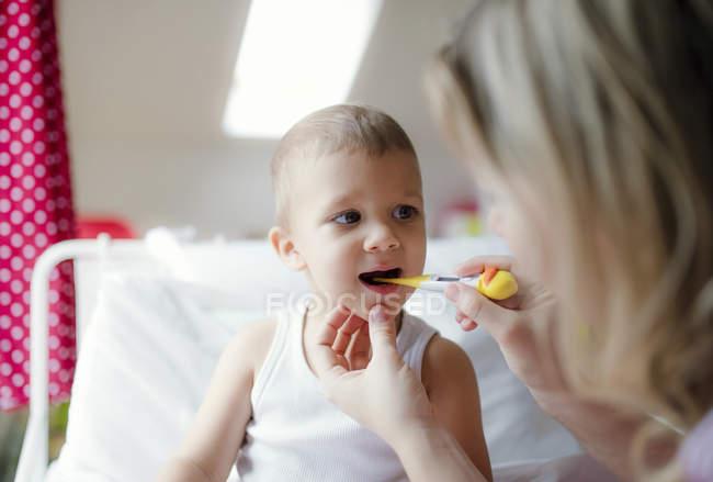 Madre che prende la temperatura del figlio del bambino a casa — Foto stock