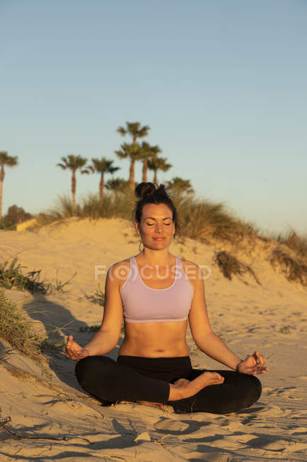 Женщина медитирует на пляже вечером — стоковое фото