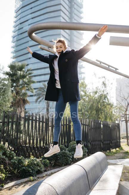 Mujeres jóvenes que equilibran y saltan en un banco de la ciudad - foto de stock