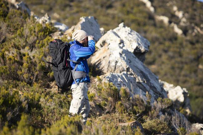 Espanha, Andaluzia, Tarifa, homem em uma viagem de caminhada nas montanhas olhando através binocular — Fotografia de Stock