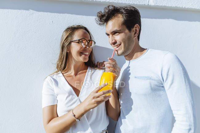 Casal feliz compartilhando um suco de laranja em um dia ensolarado — Fotografia de Stock
