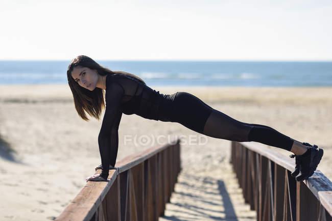Спортивная женщина отжимается на перилах деревянного моста — стоковое фото