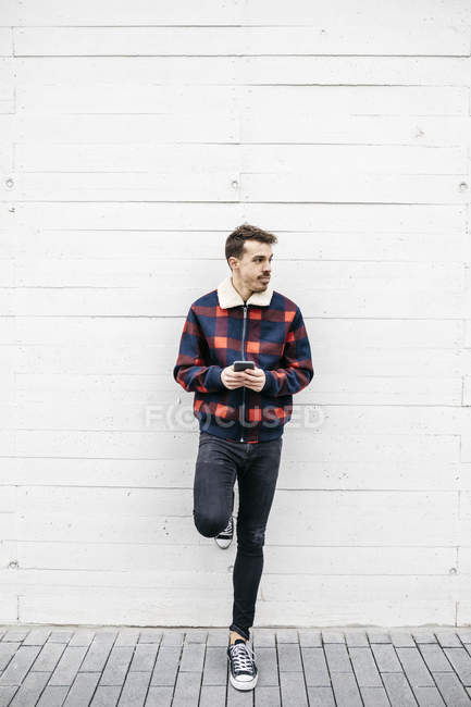 Young man with red and blue jacket using phone in a white wall — Stock Photo