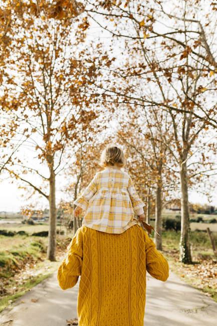 Père portant sa petite fille sur les épaules le matin, parc en automne — Photo de stock