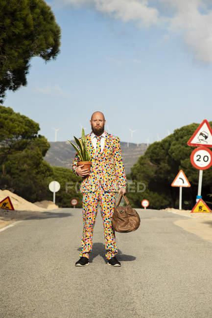Мужчина в костюме с красочными горошинками стоит на проселочной дороге с дорожной сумкой и цветочным горшком — стоковое фото