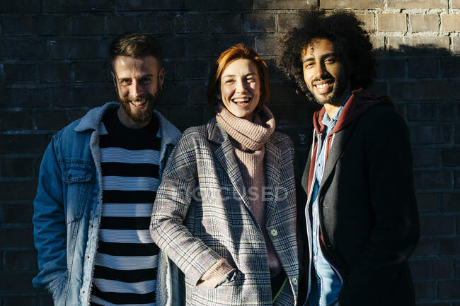 Portrait of three happy friends in shadow at a brick wall — Stock Photo