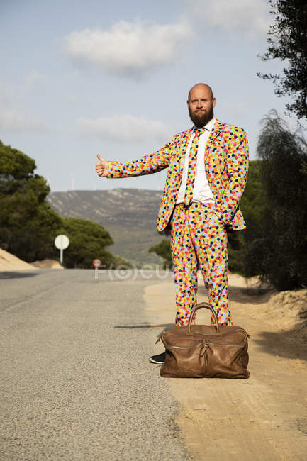 Hitchhiking man wearing suit with colourful polka-dots standing at roadside with travelling bag — Stock Photo