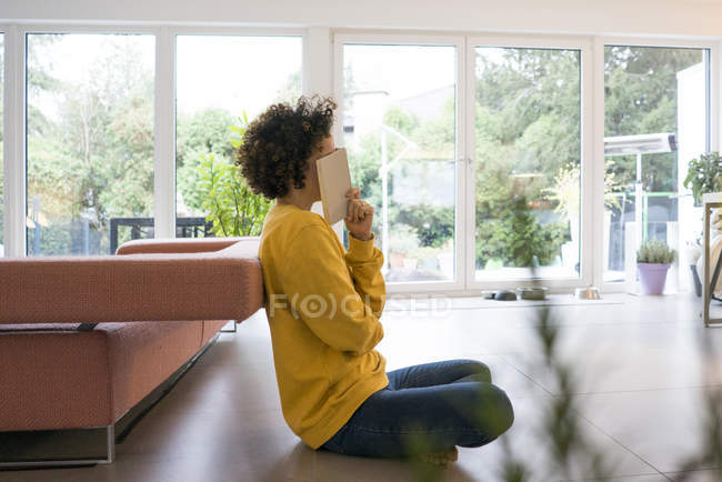 Woman with book sitting on the floor at home — Stock Photo