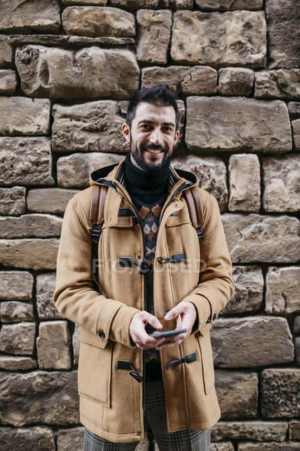 Espanha, Igualada, retrato do homem sorridente em pé na parede de pedra com telefone celular — Fotografia de Stock