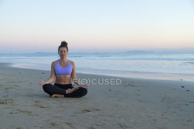 Woman meditating on the beach in the evening — Photo de stock