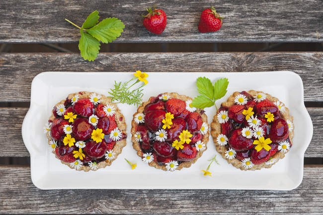 Homemade strawberry heart tartlets with daisy flowers and golden marigold, edible flowers, dark wood — Stock Photo