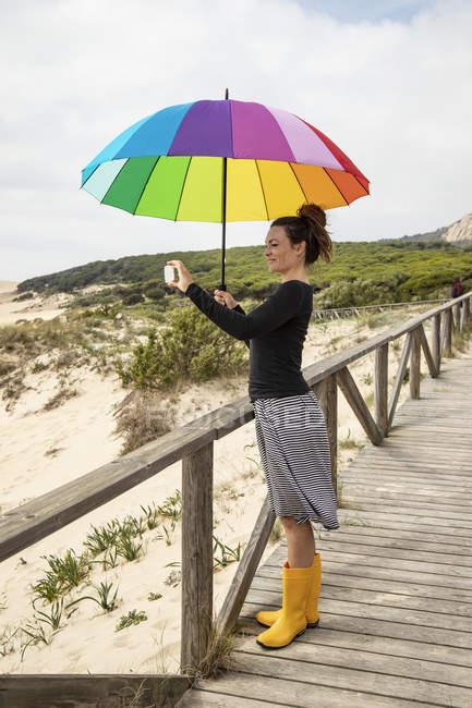 Femme avec parapluie coloré debout sur la plage, prenant un selfie — Photo de stock