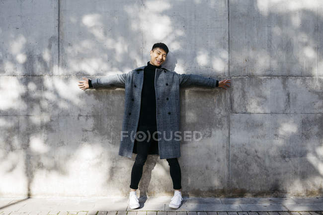 Laughing young man wearing turtleneck pullover and grey coat standing in front of concrete wall - foto de stock