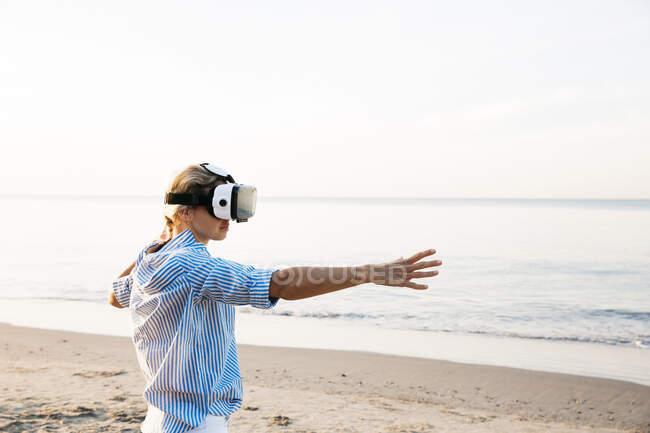 Mulher loira fazendo tipo de exercícios de ioga em uma praia na Tailândia com óculos de realidade virtual 3D — Fotografia de Stock