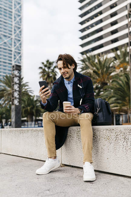 Espagne, Barcelone, homme assis dans la ville avec café à emporter et téléphone portable — Photo de stock