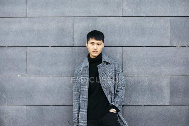 Ritratto di giovane elegante uomo che indossa maglione collo alto nero e cappotto grigio — Foto stock