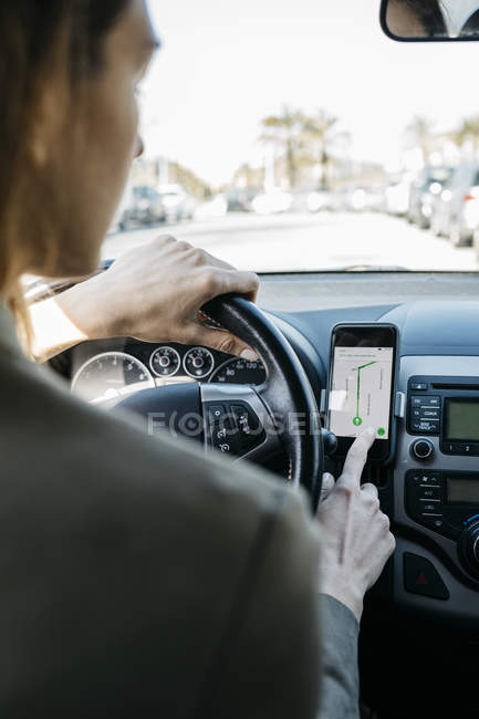 Mujer conduciendo en un coche a través de la ciudad usando una aplicación de navegación telefónica - foto de stock